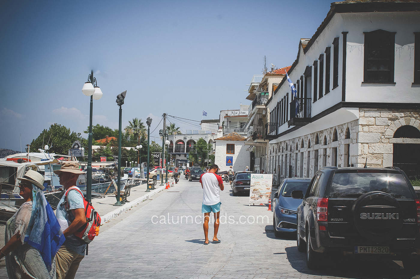A man stands in the centre of a road in a town.